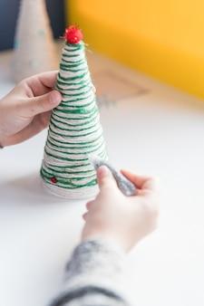 Mãos de uma menina criando árvore de natal de fio. presente de malha de natal feito à mão. árvore de natal
