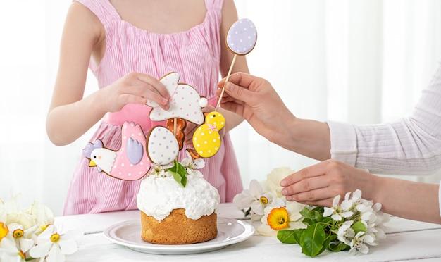 Mãos de uma menina e uma mãe no processo de decoração de um bolo festivo. o conceito de preparação para o feriado da páscoa.