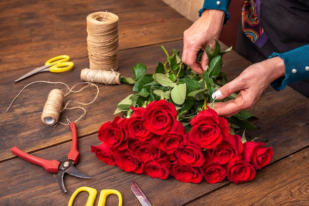 Mãos de uma mulher arrumando um buquê de flores em uma mesa