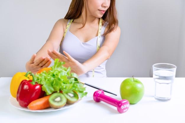 Mãos de uma mulher asiática infeliz empurrando vegetais e frutas com emoção entediada na hora da dieta