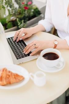 Mãos de uma mulher com café e laptop em um café ao ar livre no verão