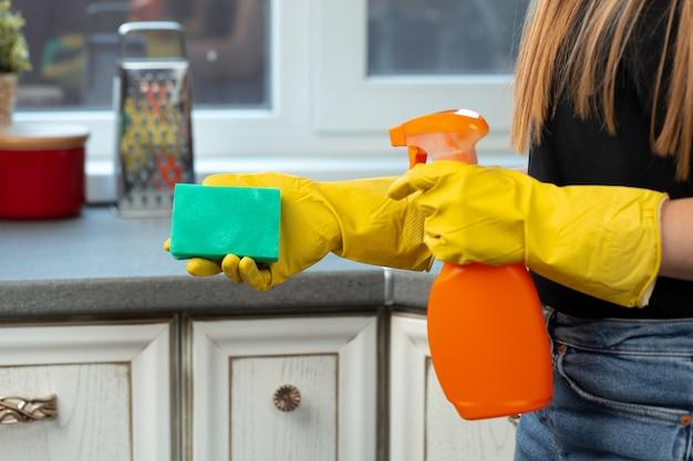 Mãos de uma mulher com luvas amarelas segurando uma esponja verde