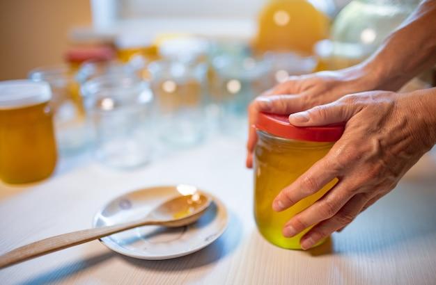 Mãos de uma mulher desconhecida fecham potes de vidro transparente com mel dourado puro e doce com tampa de borracha, em pé sobre uma grande mesa de madeira branca e ao lado de um pequeno pires com uma colher de pau