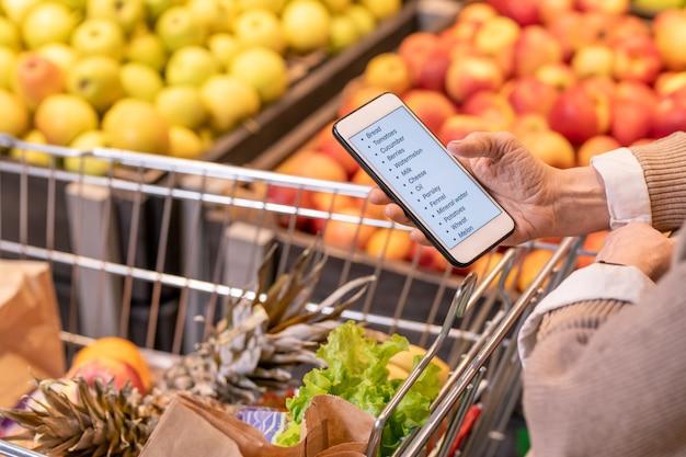 Mãos de uma mulher envelhecida contemporânea olhando a lista de compras no smartphone em cima do carrinho com frutas e vegetais frescos no supermercado