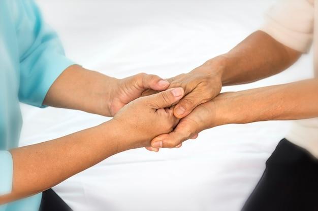 Mãos de uma mulher idosa segurando a mão de uma mulher mais jovem.