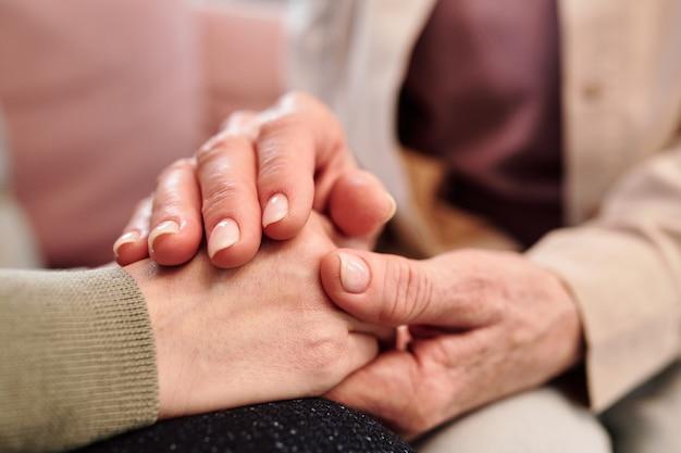 Mãos de uma mulher madura apoiando a filha