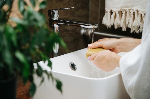 Mãos de uma mulher madura se lavando com um bloco de sabão ecológico. ela está parada na frente da pia em um banheiro.