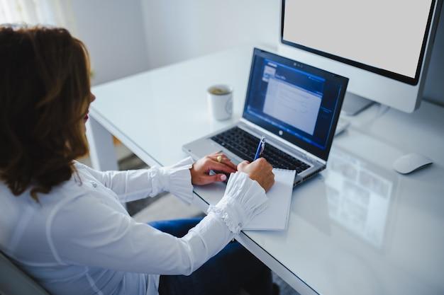 Mãos de uma mulher que trabalha em seu laptop.
