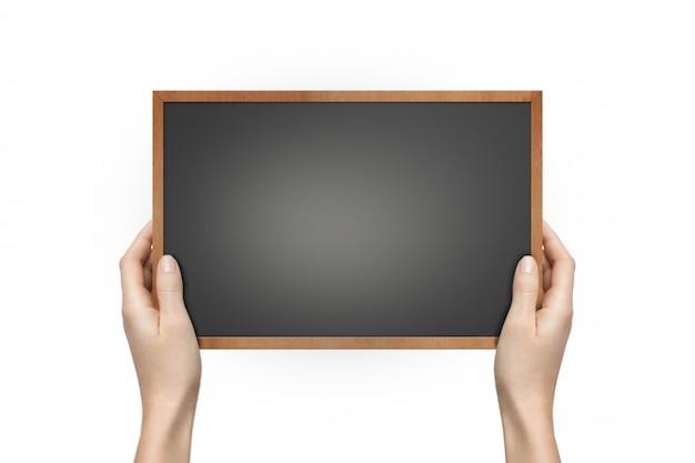 Mãos de uma mulher segurando o quadro-negro