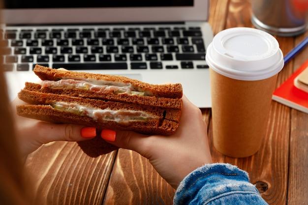 Mãos de uma mulher segurando um sanduíche acima da mesa de trabalho com o laptop aberto