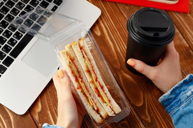 Mãos de uma mulher segurando um sanduíche acima da mesa de trabalho com um laptop