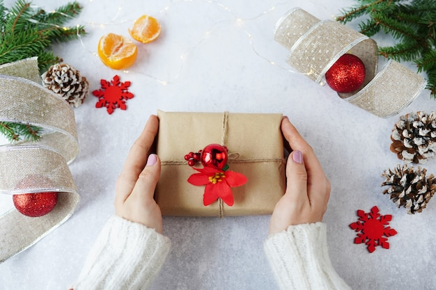 Mãos de uma mulher segurando uma caixa de presente de natal com enfeites de inverno