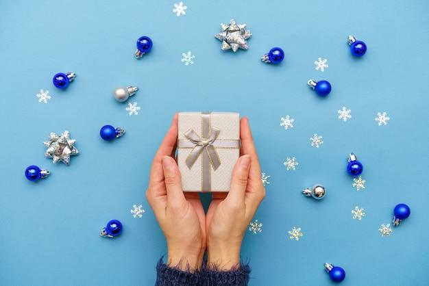 Mãos de uma mulher segurando uma caixa de presente presente, amarrada com um laço de fita sobre fundo azul ao redor da decoração da árvore de natal com bolas e flocos de neve. natal, ano novo, feriados, conceito de aniversário