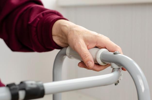 Mãos de uma mulher sênior nas alças de um andador. reabilitação e conceito de saúde.