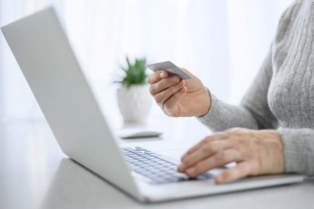 Mãos de uma mulher sênior trabalham em um laptop com cartão de crédito, usando tecnologia moderna na vida cotidiana.