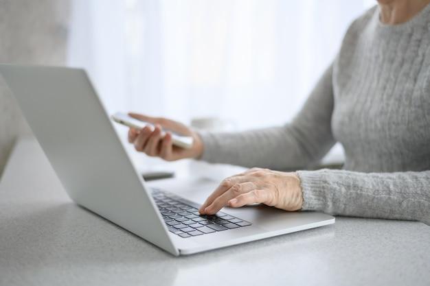 Mãos de uma mulher sênior trabalham em um laptop com telefone, usando tecnologia moderna na vida cotidiana. compras online