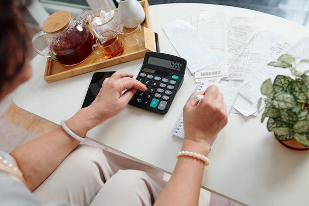 Mãos de uma mulher sênior usando calculadora para verificar as contas e somar as despesas mensais