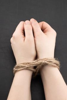 Mãos de uma mulher vítima amarrada com corda