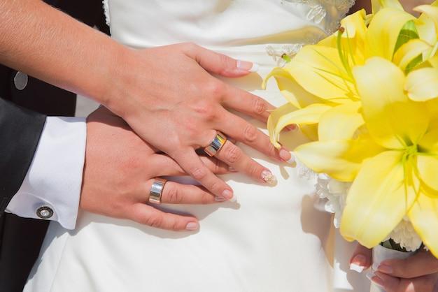 Mãos de uma noiva e do noivo com anéis de casamento e buquê de lírios amarelos