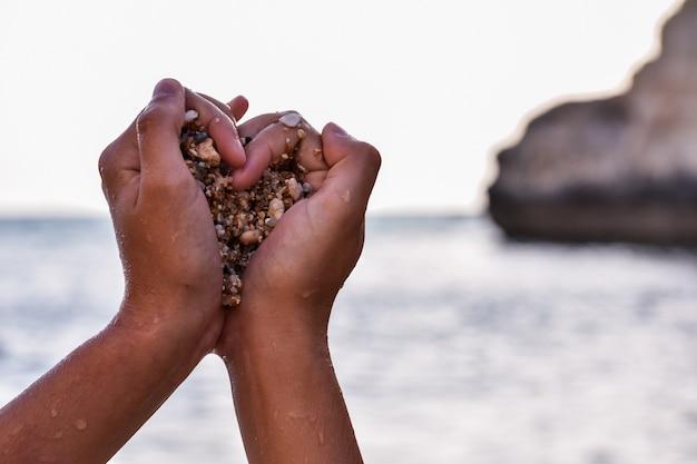 Mãos de uma pessoa negra agarrando pedras em forma de coração