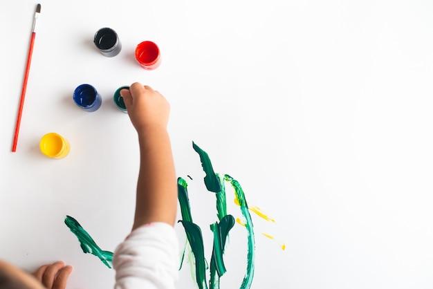 Mãos de uma pintura do rapaz pequeno com as aquarelas na folha do livro branco. garotinho com um pincel e tintas.