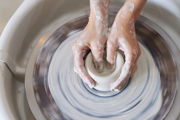 Mãos de vaso de modelagem de ceramista na vista da roda de oleiro do topo