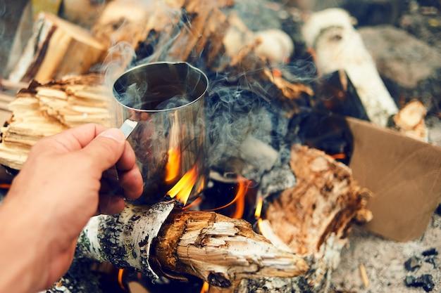 Mãos de viajante homem segurando uma xícara de chá perto do fogo ao ar livre. alpinista bebendo chá da caneca no acampamento. café cozido sobre uma fogueira na natureza. conceito de aventura, viagens, turismo e camping.