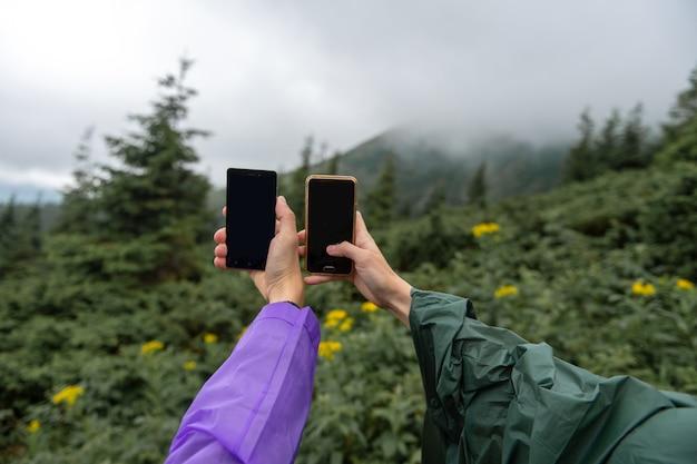 Mãos de viajantes com telefones tiram foto da natureza paisagem vista em dia chuvoso de verão. turistas em aventura de acampamento tiram selfie com celulares. momentos felizes.