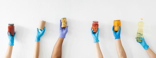 Mãos de voluntário com luvas segurando provisões para doação