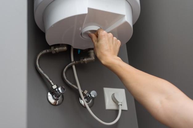 Mãos, definindo a temperatura da água na caldeira elétrica do aquecedor
