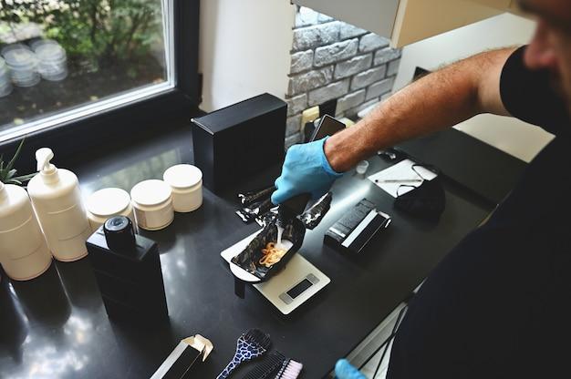 Mãos derramando um pigmento de cor líquido e misturando ingredientes para tingir o cabelo profissional