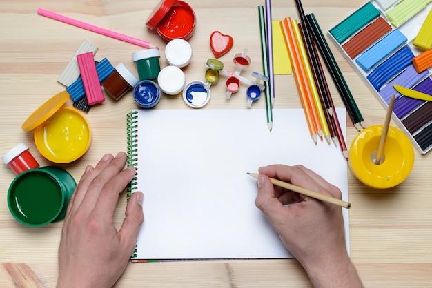 Mãos desenhando com tintas e marcadores em papel branco