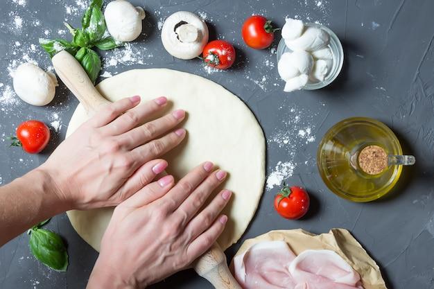 Mãos desenrolando massa de pizza, ingredientes de pizza crua, rolo, base de massa
