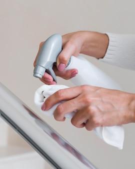 Mãos desinfetando corrimão