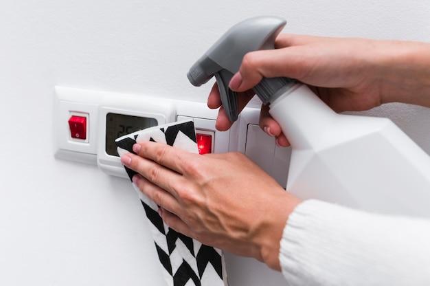 Mãos desinfetando interruptores de luz