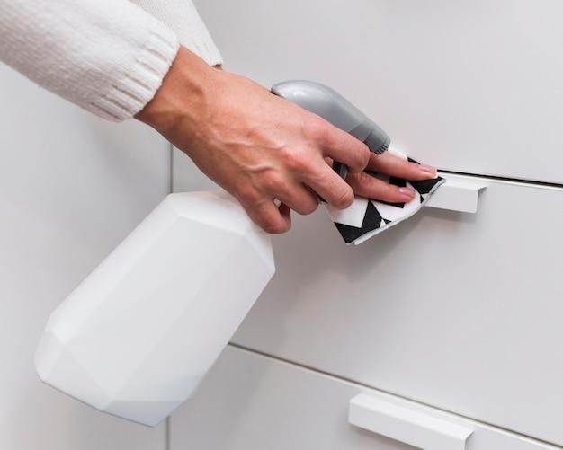 Mãos desinfetando puxadores de móveis