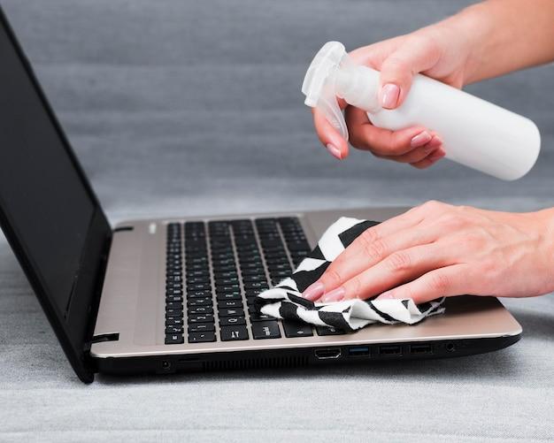 Mãos desinfetando teclado de laptop