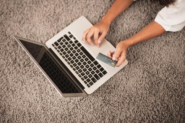 Mãos digitando e segurando um cartão de crédito no chão