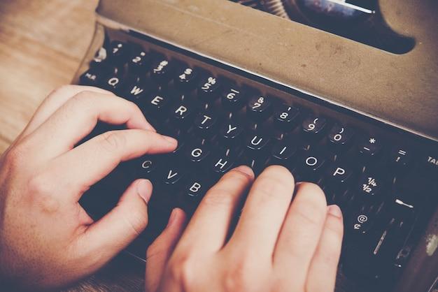 Mãos digitando na máquina de escrever vintage na mesa de madeira.