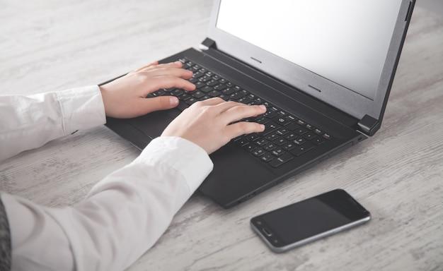 Mãos digitando no teclado do laptop na mesa do escritório.