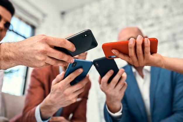 Mãos diversas masculinas e femininas segurando telefones celulares, empresários multirraciais usando software de aplicativos de smartphones, conceito de usuários e dispositivos, comunicação móvel.
