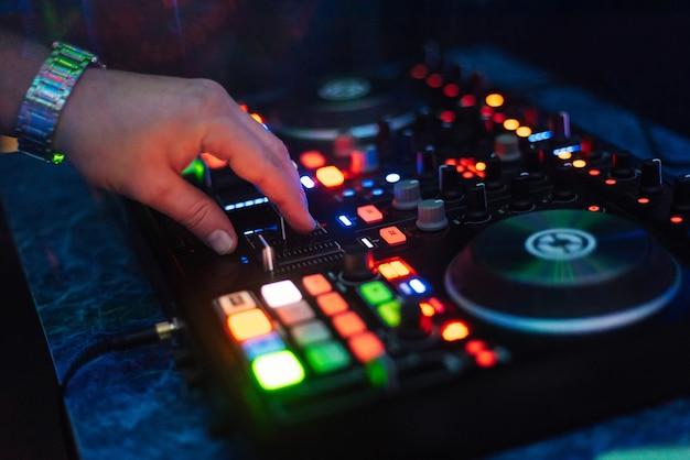 Mãos dj tocando e mixando músicas no controlador de música em uma festa