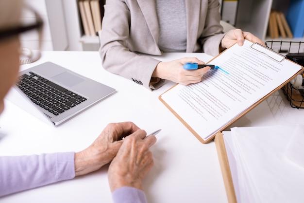 Mãos do agente de seguros sublinhando a frase importante no documento por um marcador azul enquanto a explica ao cliente sênior
