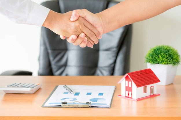 Mãos do agente e cliente apertando as mãos após contrato assinado comprar novo apartamento.