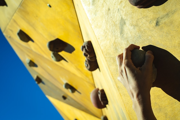 Mãos do alpinista presas aos suportes de uma parede de escalada ao ar livre.