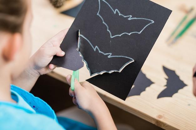 Mãos do aluno do ensino fundamental cortando o bastão de halloween de um papel preto enquanto está sentado à mesa de madeira na aula