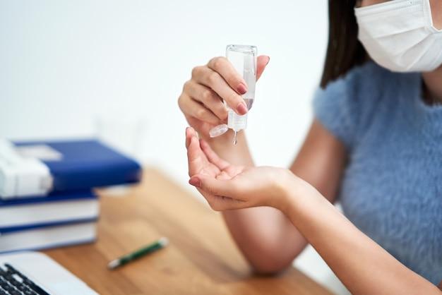 Mãos do aluno usando gel desinfetante para as mãos