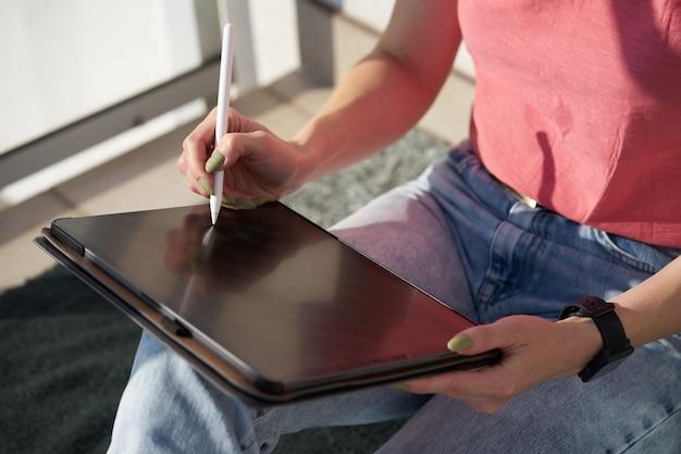 Mãos do artista digital mulher caucasiana, desenho sobre tablet, sentado na manta. conceito freelance