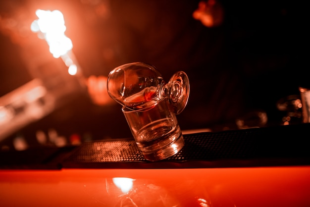 Mãos do barman, taça de vidro no balcão do bar