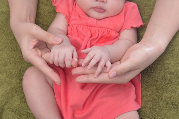 Mãos do bebê dormindo nas mãos da mãe